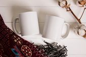 Two white mugs pair of cups Mockup. Cozy atmosphere wooden background cotton and wool decorations for winter gifts. poster