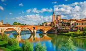 Panoramic view to Bridge Ponte Pietra in Verona on Adige river. Veneto region. Italy. Sunny summer day panorama and blue dramatic sky with clouds. Ancient european italian terracotta color houses poster