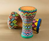 Two decorated colorful pottery goblet drums (chalice drum tarabuka darbuka) on background of wooden table with vanishing shadow lines poster