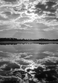 Black and white photograph - dramatic sky and reflection in the water