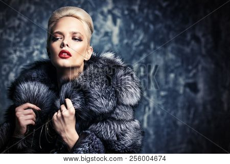Beautiful woman in luxurious fur coat posing in studio. Luxury, rich lifestyle. Fashion shot.
