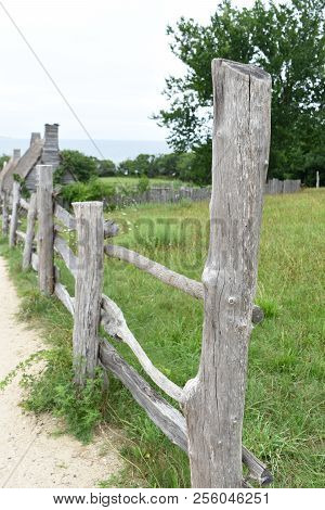 Beautiful Rustic Fencing Along A Grass Pasture In Plymouth.