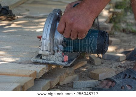 Electric Circular Saw Is Being Cut A Piece Of Wood By Carpenter. Construction Details Of Male Worker