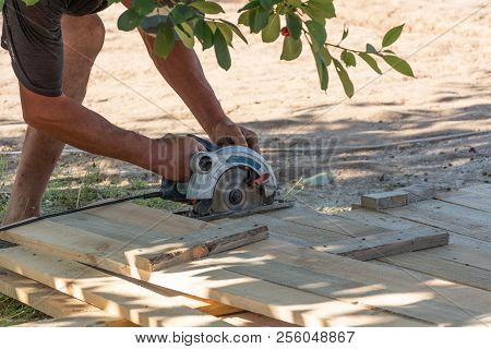 Building A Formwork For The Fence. Carpenter Using A Circular Saw To Cut A Wood Board.