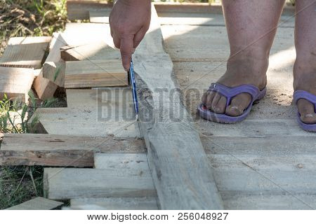 Carpenter's Hands Measuring A Wooden Board Close-up Image With The Hands Of A Man And Makes A Mark W