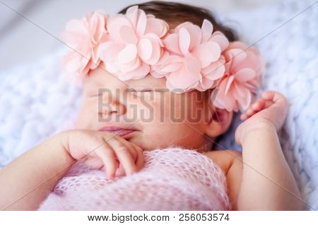 Cute Sleeping Newborn Caucasian Baby Girl A Pink Flower Head Bow. Sweet Infant Girl Smiling In Her S