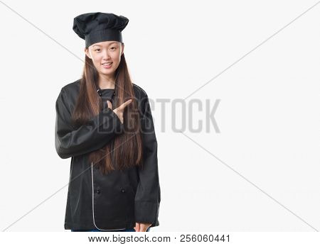 Young Chinese woman over isolated background wearing chef uniform cheerful with a smile of face pointing with hand and finger up to the side with happy and natural expression on face