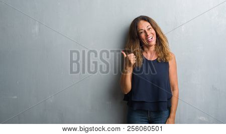 Middle age hispanic woman standing over grey grunge wall smiling with happy face looking and pointing to the side with thumb up.