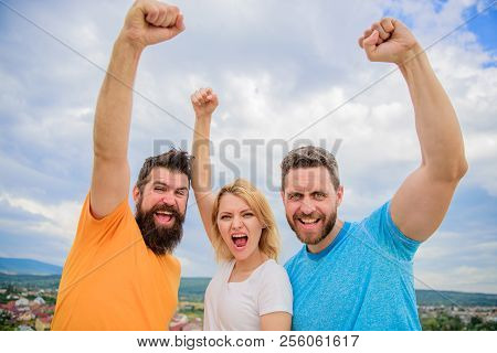 Woman And Men Look Confident Successful Sky Background. Threesome Stand Happy Confidently With Raise