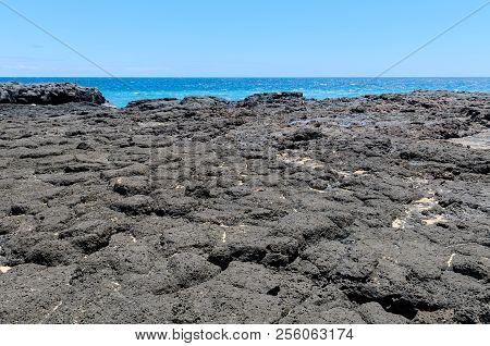 Lava Fields With A Distant Ocean And Clear Blue Sky. Kauai, Hawaii