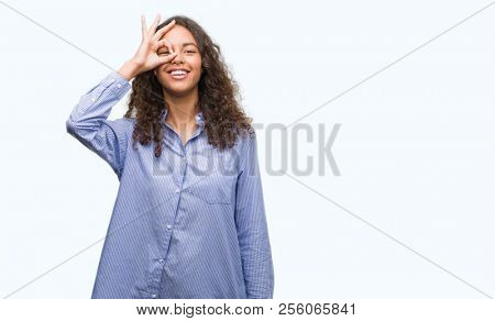 Young hispanic business woman doing ok gesture with hand smiling, eye looking through fingers with happy face.