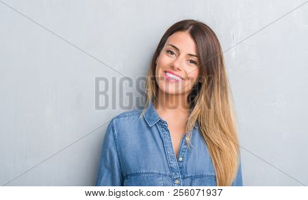 Young adult woman over grey grunge wall wearing denim outfit with a happy face standing and smiling with a confident smile showing teeth
