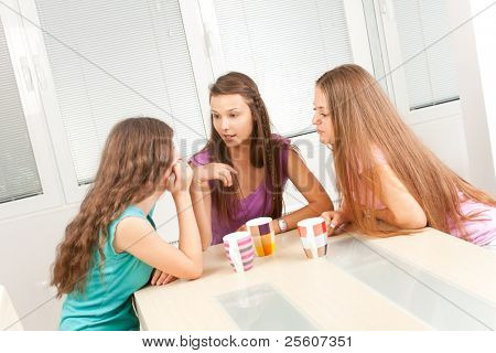 Three young female friends sitting in the living room and having talk.