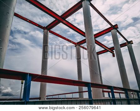 Rusty Metal Construction On The Sky Background. Rusty Metal Pier Support. Attractive View Under The