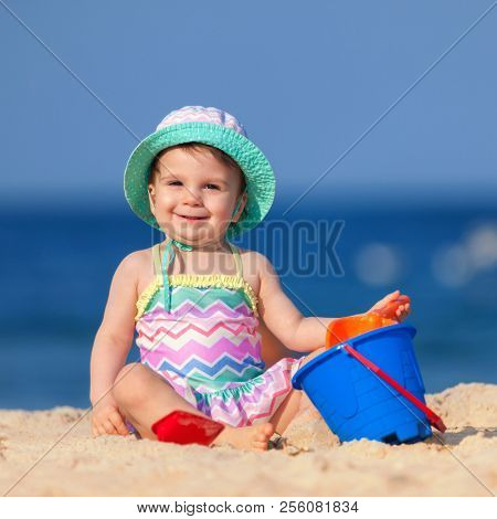 Happy childhood, happy family vacation. Cute child on the sea background. Happy little girl playing with sand on the beach of sea. Summer vacation. Summer lifestyle
