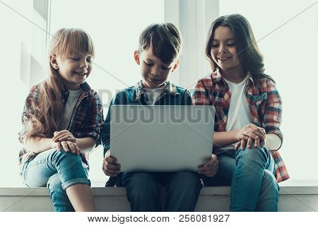 Happy Children Use Laptop Sitting On Windowsill. Two Girls Near Boy Look At Notebook While Prepearin