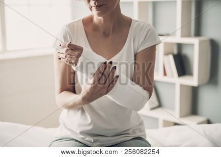 Close-up Of Female Broken Arm In Plaster Cast. Caucasian Injured Woman In White T-shirt Sitting And