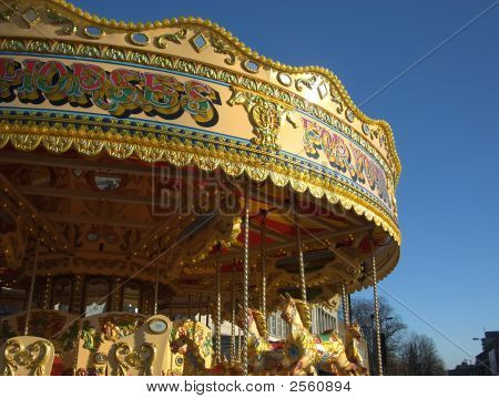 A golden coloured fairground carousel ride set against a deep blue sky. poster