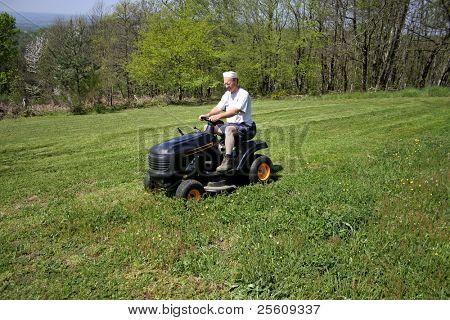 man cutting grass in a field