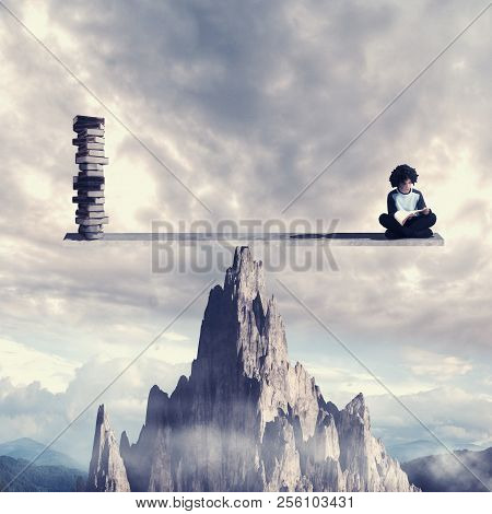 Stundent Reading A Book On Balance Scale Above A Mountain Rock. Knowledge Is Power Concept.