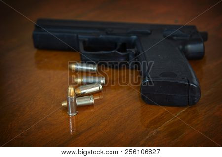 .38 Mm Handgun And Bullets Strewn On The Rustic Wooden Table Background. Gun With Ammunition On Wood