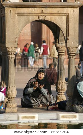 DEHLI - FEBRUARY 11. Muslim women praying in traditional clothing at Jama Masjid mosque on February 11, 2008 in Dehli, India. It's the largest mosque in India with millions of visitors each year.