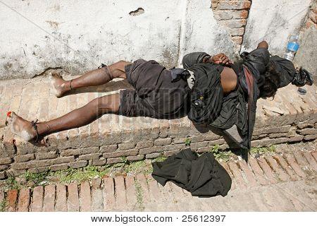 BHAKTAPUR, NEPAL- APRIL 13: A beggar sleeps in the old streets of Bhaktapur in Bhaktapur, Nepal on April 13, 2008. Bhaktapur is located about 20 km east of Kathmandu.