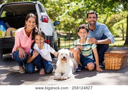 Happy family on a picnic sitting next to their car on a sunny day