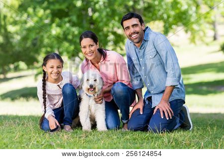 Portrait of happy family enjoying together with their pet dog in park