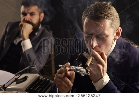Man Lighting Cigar From Burning Banknote. Businessman Smoking Cigar At Business Meeting. Squander Co