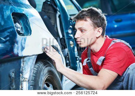 automotive repair. mechanic puttying car body poster