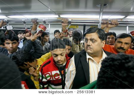 DELHI - JANUARY 19: Men standing in a crowded train carriage  on January 19, 2008 in Delhi, India. Nearly 1 million passengers use the metro daily.