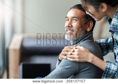 Smiling Happy Older Asian Father With Stylish Short Beard Touching Daughter's Hand On Shoulder Looki