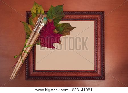 Frame, Brushes And Colorful Autumn Leaves On Wooden Background