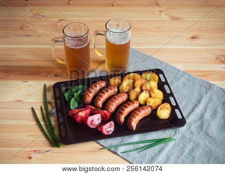 Mugs Of Beer With Grilled Pork  Sausages, Roasted Potato And Fresh Tomatoes.