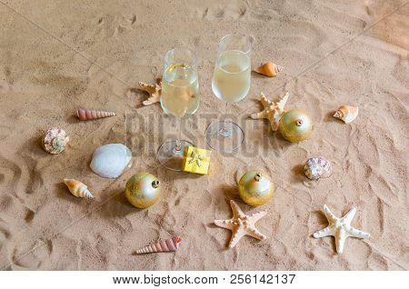 Champagne Glasses, Chrismas Balls And Gift On Beach. Christmas And New Year Celebration.