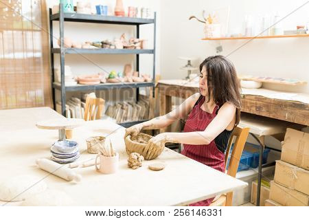 Mid adult female artisan molding clay at table in pottery workshop poster