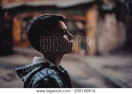 Pre-teen Boy On A Street In A Big City Next To A High-rise Building Alone. Lifestyle Of A Serious Lo