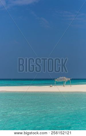 Amazing Blue Water In A Desert Island With Blue Sky Day And Simple Wood Hut
