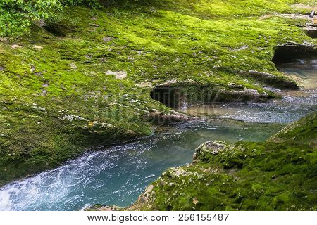 Small Mountain River Flowing Through The Green Forest In Stone Bed. Rapid Flow Over Rock Covered Wit