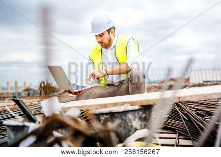 Construction Engineer Planning With Laptop, Using Technology At Construction Site