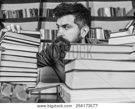 Teacher Or Student With Beard Sits At Table With Glasses, Defocused. Bibliophile Concept. Man On Str