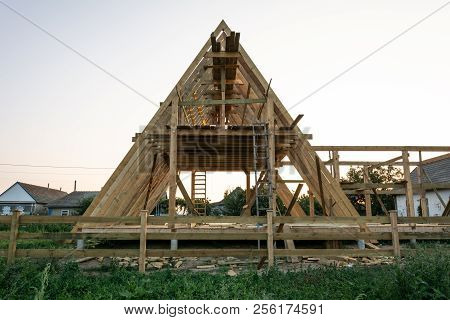 Wooden Rafters Of A New Home Under Construction At Sunset. New House Construction Interior With Expo