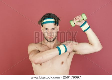 Man With Naked Body And Strong Biceps Holds Dumbbell And Points At Muscle On Purple Background. Spor