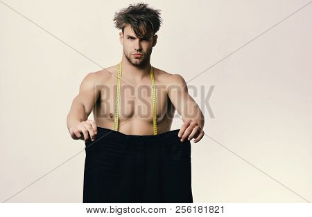 Athlete With Messy Hair And Half Naked Torso. Man Holds Black Jeans Of Large Size And Yellow Measuri