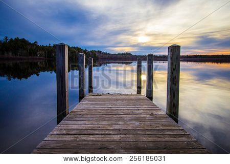Summer Sunset Over Lake.. Sunset Reflected In The Blue Water Of Brevort Lake With Wooden Dock In The