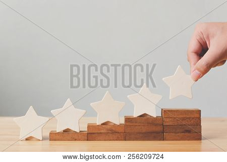 Hand Putting Wooden Five Star Shape On Table. The Best Excellent Business Services Rating Customer E