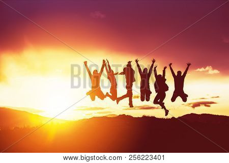 Group Of Happy Friends Having Fun And Jumping Against Sunset. Silhouettes Concept