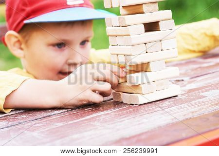 Caucasian Kid Is Playing Wood Blocks Tower Game For Practicing Physical And Mental Skill.