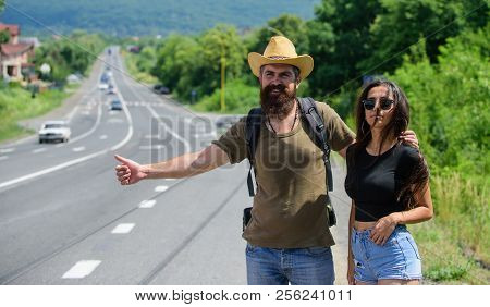 Travellers Try To Stop Car. Hitchhiking Is One Of Cheapest Ways Of Traveling. Couple Hitchhikers Tra